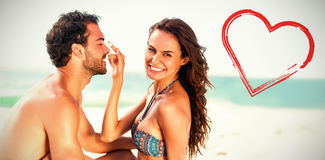 Print against happy girlfriend putting sunscreen on boyfriends nose Royalty Free Stock Image