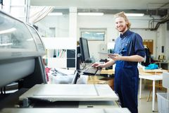 Print factory. Portrait of man doing orders of his clients on printing machine stock photography