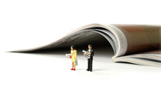 Print Media Readers. A media concept image of two business newspaper readers against a magazine in background. Copy space royalty free stock images
