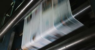 Print plant factory. Newspaper printing at a plant. Newspaper printed on a printing house machine. Close up stock footage