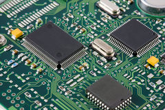 Printed Circuit Board. An electronics printed circuit baord showing surface mount components including quad flat pack ICs, resistors, capacitors and crystals royalty free stock photos