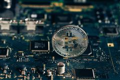 Printed circuit board with a chip and a bitcoin stock photo