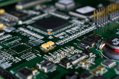 Printed Circuit board from a computer in black with green lines.  Stock Photo