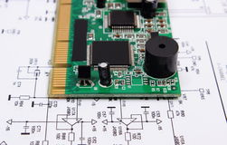 Printed circuit board lying on diagram of electronics, technology Royalty Free Stock Images