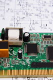 Printed circuit board lying on diagram of electronics, technology Royalty Free Stock Photography