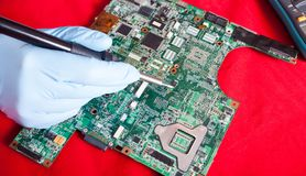 Printed circuit board, PCB over red table. With repairmans hand in bkue gloves Royalty Free Stock Image