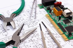 Printed circuit board and precision tools on diagram of electronics, technology Royalty Free Stock Photo