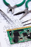Printed circuit board and precision tools on diagram of electronics, technology Stock Photos
