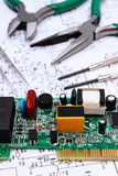 Printed circuit board and precision tools on diagram of electronics, technology Royalty Free Stock Image