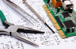 Printed circuit board and precision tools on diagram of electronics, technology Stock Images