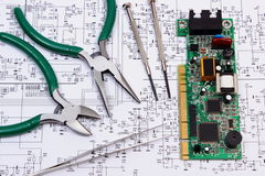 Printed circuit board and precision tools on diagram of electronics, technology Stock Photography