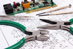 Printed circuit board and precision tools on diagram of electronics, technology Royalty Free Stock Photography