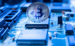 Crypto currency bitcoin on printed circuit board. On a printed circuit motherboard is silver coin of a digital crypto  currency - Bitcoin Royalty Free Stock Photography