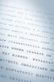 Printed codes. Close up of random codes of numbers and letters on paper. Narrow DOF Stock Photo