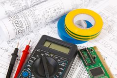Printed drawings of electrical circuits, digital multimeter, electronic board and insulating tape. stock photo