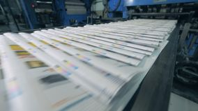 Printed magazines are moving along the transporter. Printing newspapers in typography. Printed magazines are moving along the transporter. 4K stock footage