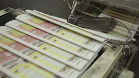 Printed newspaper conveyor working inside print factory stock footage