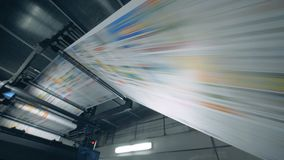 Printed newspaper going on a rolling conveyor, print office equipment. 4K stock video footage