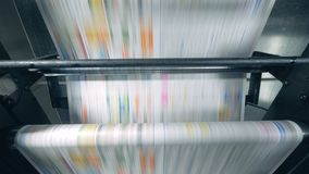 Printed newspaper rolling on a conveyor, typographical equipment works. 4K stock footage