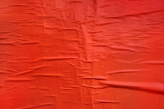 Printed red poster paper texture. Crumpled billboard material glued to a wall, useful as background stock image