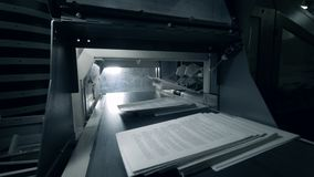 Printed sheets moving on a long conveyor, typographic equipment. stock footage