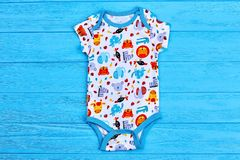 5e23d061902 Printed soft newborn bodysuit. Clothes for the newborn on blue wooden  background. Newborn kids