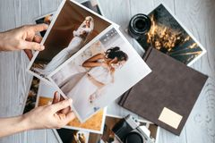 Printed wedding photos with the bride and groom, a vintage black camera, photoalbum and woman hands with two photos royalty free stock photography