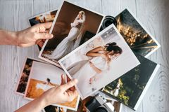 Printed wedding photos with the bride and groom, a vintage black camera and woman hands with two photos. Printed wedding photos with the bride and groom, a stock images