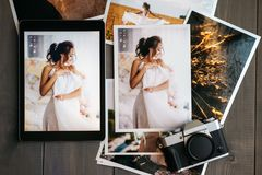 Printed wedding photos with the bride, a vintage black camera and a black tablet with a picture of bride. On wooden background royalty free stock photos