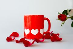 Printed white hearts on red coffee cup and rose stock images