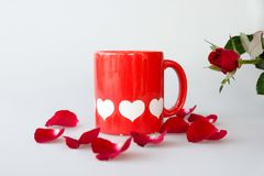 Printed white hearts on red coffee cup and rose royalty free stock photos