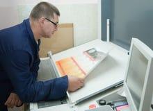 Printer checking a print run. At table Royalty Free Stock Image