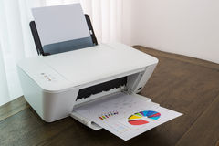 Printer with financial documents. On a wood table stock photography