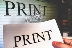 Printer hand hold a print sheet with word processor software screen on background in office stock photo