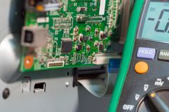 Printer motherboard and multimeter. Repair of office equipment royalty free stock images