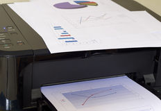 Printer printing business report. Printer Printer and graphs business report royalty free stock photography