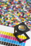 Printers magnifying glass. Shallow depth of field image of a printers loupe on printed sheet.  Focus is on the top of the loupe Royalty Free Stock Photo