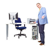 Printing is easy. A man demonstrating how easy it is to print professional documents by taking a sheet of paper out of a printer in an office There are more royalty free stock image