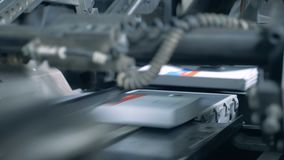 One machine moves books on a printing conveyor, close up. Printing equipment moving books on a line stock footage