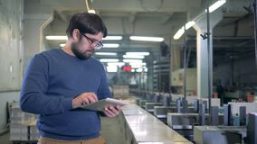 Printing house worker is standing next to industrial machines stock footage
