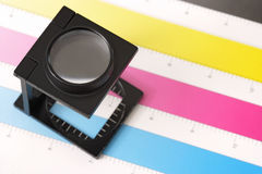 Printing inspection. Shallow depth of field image of a printers loupe on printed sheet.  Focus is on the top of the loupe Royalty Free Stock Photo