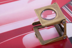 Printing loupe. High angle view of metal printing loupe over colorful pink and red paper Stock Photography