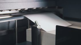 Printing press machine takes sheet of paper in action in the printing production line. Slow motion royalty free stock photography