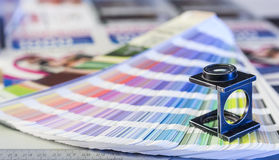Printing process with magnifying glass and color swatches. Color management in printing process with magnifying glass and color swatches Stock Image
