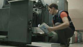 Printingprocess i maskin av printingtransportören - arbetarmellanläggspapper täcker lager videofilmer