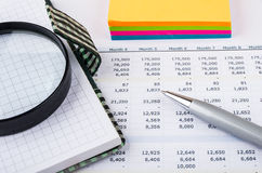 Printout with costs. Adhesive paper, notepad and magnyfying glass. Analysing printout with costs. Adhesive paper, notepad and magnyfying glass royalty free stock image