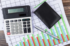 Printout with diagrams, electronic calculator, notepad and ballp Stock Images