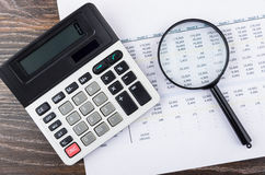 Printout, electronic calculator and magnifying glass on wooden t Stock Photography