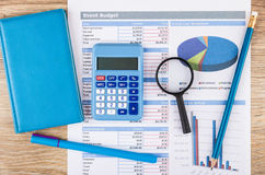Printout of event budget, calculator, notepad, magnifying glass. And pen on wooden table. Top view stock photo