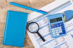 Printout of event budget, calculator, notepad, pen and magnifying glass. On wooden table. Top view royalty free stock image